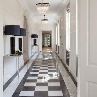 На фото: огромный коридор в стиле современная классика с бежевыми стенами и мраморным полом с