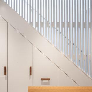 Bild på en mellanstor funkis hall, med vita väggar, ljust trägolv och brunt golv