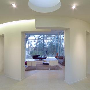 Пример оригинального дизайна: большой коридор в стиле модернизм с белыми стенами и полом из известняка
