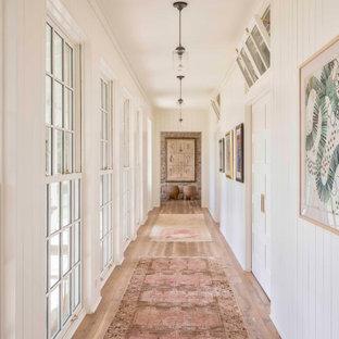 Cette image montre un couloir rustique avec un mur blanc, un sol en bois brun, un sol marron et du lambris de bois.