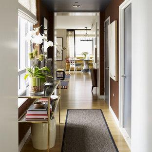Imagen de recibidores y pasillos contemporáneos con paredes marrones y suelo de madera clara