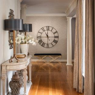 Cette photo montre un couloir chic avec un mur gris, un sol en bois brun, un sol marron et du papier peint.