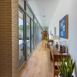 Photo of a large midcentury hallway in Dallas with beige walls, medium hardwood floors and brown floor.
