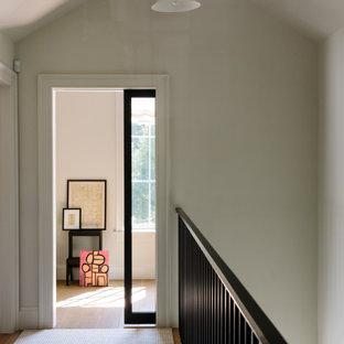 サンフランシスコのカントリー風おしゃれな廊下 (グレーの壁、無垢フローリング、茶色い床、三角天井) の写真