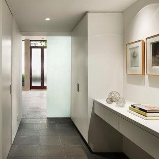Exempel på en modern hall, med vita väggar och grått golv