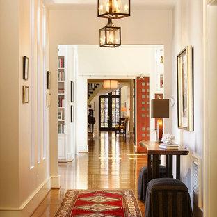 Inspiration för en mycket stor vintage hall, med mellanmörkt trägolv och vita väggar