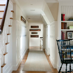 Example of a large classic medium tone wood floor hallway design in Boston with white walls