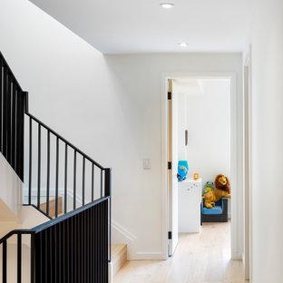 トロントの中くらいのモダンスタイルのおしゃれな廊下 (白い壁、淡色無垢フローリング、白い床、三角天井) の写真