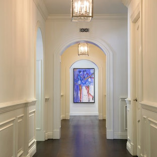 Example of a mid-sized classic dark wood floor and brown floor hallway design in Los Angeles with white walls