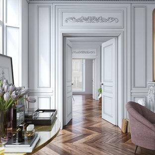 На фото: коридор среднего размера в викторианском стиле с белыми стенами и темным паркетным полом с
