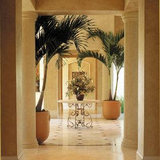 Exemple d'un très grand couloir méditerranéen avec un mur beige et un sol en travertin.