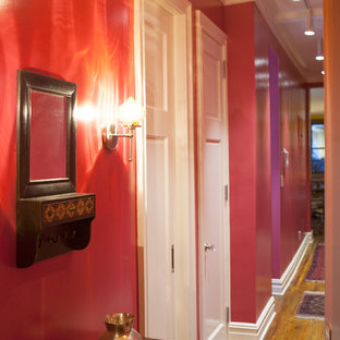 Inspiration for a small eclectic hallway in New York with red walls and dark hardwood floors.