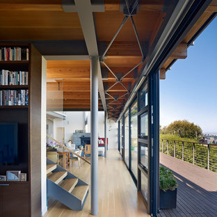 This is an example of a large modern hallway in San Francisco with white walls and medium hardwood floors.