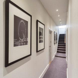ロンドンのトラディショナルスタイルのおしゃれな廊下 (白い壁、カーペット敷き、紫の床) の写真