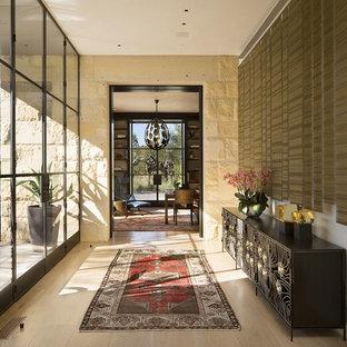 Idéer för att renovera en stor tropisk hall, med vita väggar, ljust trägolv och beiget golv