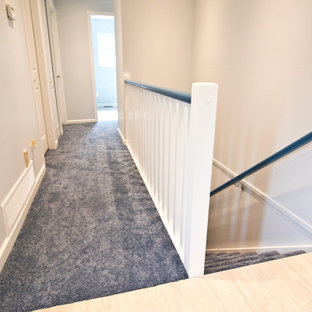 Inspiration for a mid-sized timeless carpeted and blue floor hallway remodel in Vancouver with white walls