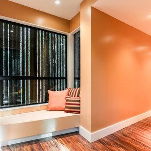 Idee per un grande ingresso o corridoio tradizionale con pareti arancioni, pavimento in legno massello medio e pavimento arancione