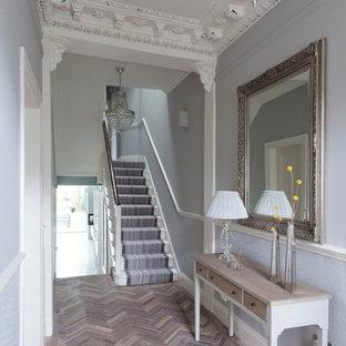 Exempel på en klassisk hall, med grå väggar och ljust trägolv