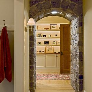 Inspiration pour un couloir victorien avec un mur beige et un sol en bois clair.
