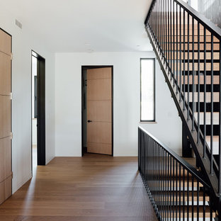 Inspiration for a mid-sized mid-century modern medium tone wood floor and brown floor hallway remodel in Other with white walls