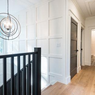 チャールストンの広いモダンスタイルのおしゃれな廊下 (白い壁、淡色無垢フローリング、茶色い床) の写真