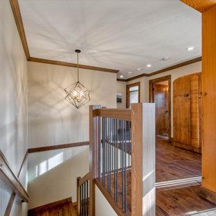 Inspiration pour un couloir chalet de taille moyenne avec un mur beige, un sol en bois brun, un sol marron et un plafond en poutres apparentes.