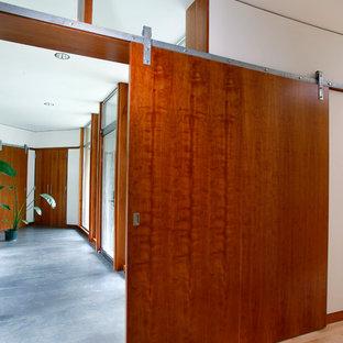 Пример оригинального дизайна: огромный коридор в стиле модернизм с белыми стенами, полом из сланца и синим полом