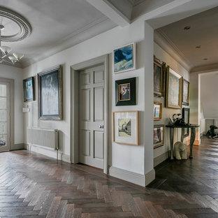 Klassisk inredning av en mycket stor hall, med vita väggar, mörkt trägolv och brunt golv