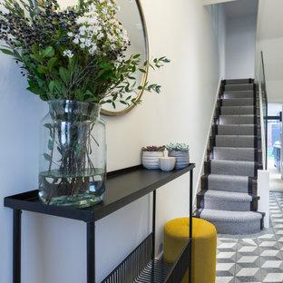 Cette image montre un petit couloir design avec un mur blanc, un sol en terrazzo et un sol bleu.