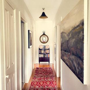 Idée de décoration pour un petit couloir design avec un mur blanc, un sol en bois foncé, un sol marron, un plafond décaissé et un mur en parement de brique.