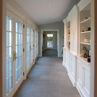 На фото: коридор среднего размера в классическом стиле с белыми стенами, полом из сланца и серым полом с