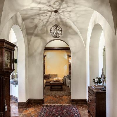 Example of a tuscan terra-cotta tile hallway design in Dallas