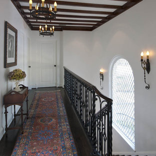 Example of an eclectic dark wood floor hallway design in Dallas with white walls