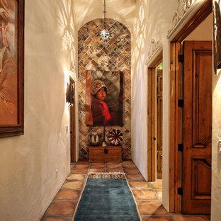 ロサンゼルスのサンタフェスタイルのおしゃれな廊下 (ベージュの壁、テラコッタタイルの床) の写真