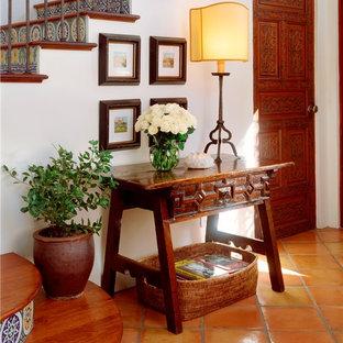 Diseño de recibidores y pasillos mediterráneos con paredes blancas, suelo de baldosas de terracota y suelo naranja