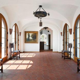 Immagine di un ampio ingresso o corridoio mediterraneo con pareti bianche, pavimento in terracotta e pavimento marrone