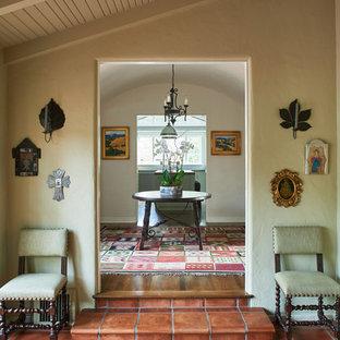 Réalisation d'un grand couloir méditerranéen avec un mur beige, un sol en carreau de terre cuite et un sol orange.