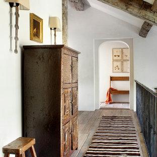 Ejemplo de recibidores y pasillos rurales con paredes blancas y suelo de madera en tonos medios