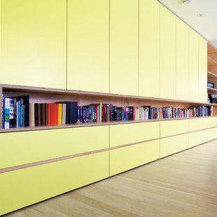 Exemple d'un grand couloir moderne avec un mur blanc et un sol en bois clair.
