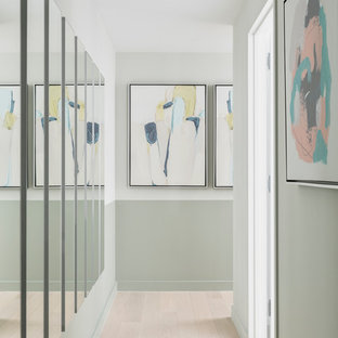 This is an example of a mid-sized midcentury hallway in New York with light hardwood floors, green walls and beige floor.
