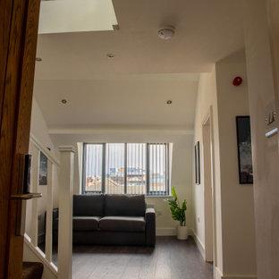 На фото: большой коридор в современном стиле с белыми стенами, ковровым покрытием, серым полом, балками на потолке и кирпичными стенами