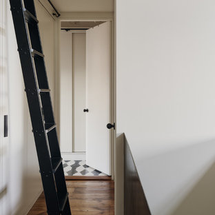 Mid-sized danish medium tone wood floor hallway photo in New York with white walls