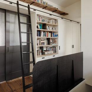 Mid-sized danish medium tone wood floor hallway photo in New York with white walls