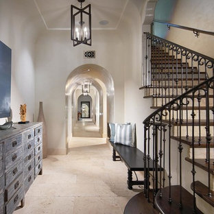 Inspiration for a mid-sized mediterranean travertine floor and beige floor hallway remodel in Orange County with white walls