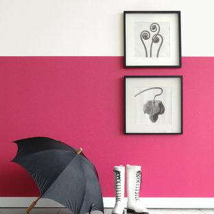 Cette photo montre un couloir moderne avec un mur rose et béton au sol.