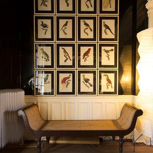 Cette image montre un grand couloir bohème avec un mur noir et un sol en bois brun.