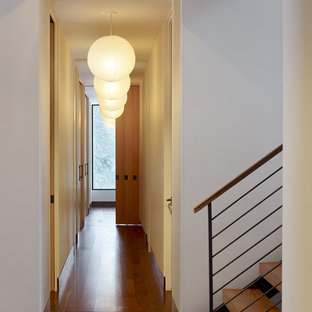 Trendy dark wood floor hallway photo in Sacramento with white walls