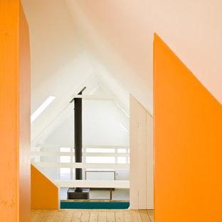 Inspiration pour un couloir nordique avec un mur orange et un sol en bois clair.