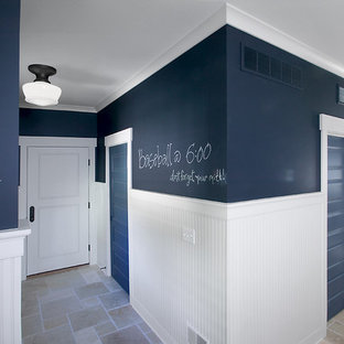 This is an example of a large beach style hallway in Grand Rapids with blue walls, travertine floors and grey floor.