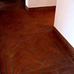 Пример оригинального дизайна: коридор среднего размера в средиземноморском стиле с белыми стенами, полом из терракотовой плитки и красным полом